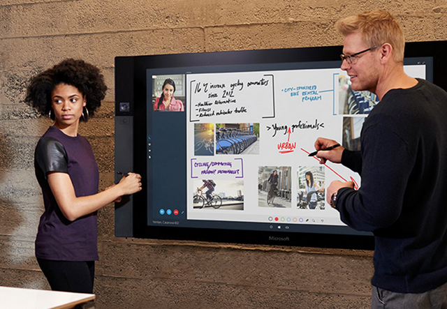 Two people working on a Microsoft Surface Hub