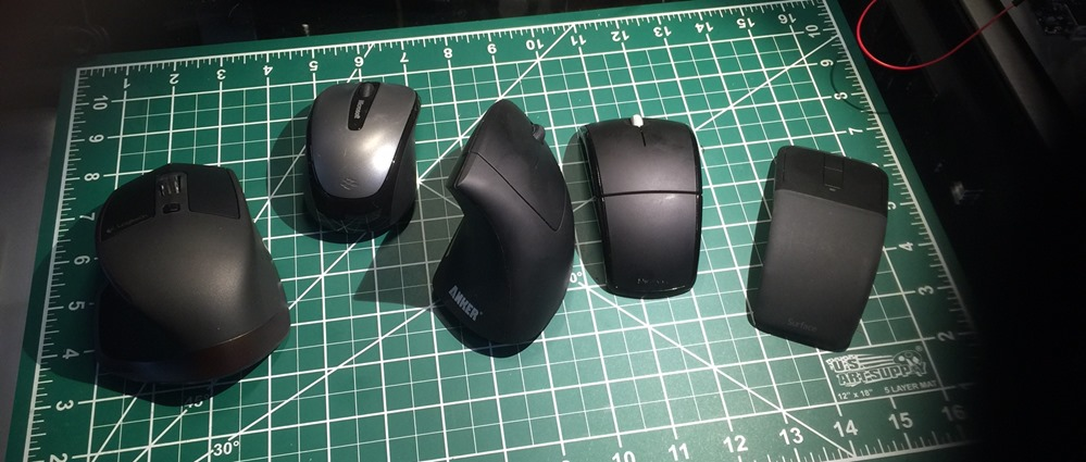 Five black computer mice, laid out left to right, and described in order below